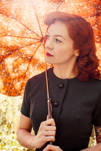Sweden, Redheaded woman holding umbrellaの写真素材 [FYI02198493]