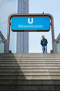 Germany, Berlin, Alexanderplatz, Man standing at underground entranceの写真素材 [FYI02198553]