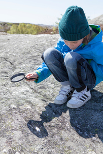 Sweden, Gothenburg Archipelago, Vastergotland, Styrso, Boy (10-11) with magnifying glass looking atの写真素材 [FYI02198576]