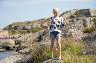 Sweden, Vastergotland, Lerum, Blonde girl (10-11) with fishing rod toy on rockの写真素材 [FYI02198613]
