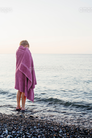 Sweden, Gotland, Lickershamn, Boy (8-9) wrapped in towel standing at seashore at sunsetの写真素材 [FYI02198664]