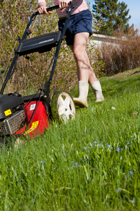 Sweden, Ostergotland, Vikbolandet, Low-section of woman mowing lawnの写真素材 [FYI02198707]