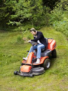 Finland, Uusimaa, Espoo, Man on lawn mower in parkの写真素材 [FYI02198784]