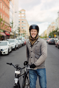 Sweden, Sodermanland, Stockholm, Sodermalm, Hornstull, Mid adult man standing by his bicycle on streの写真素材 [FYI02198799]