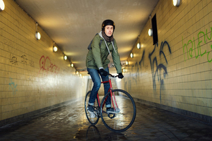 Sweden, Sodermanland, Stockholm, Sodermalm, Slussen, Mid adult man riding bicycle through tunnelの写真素材 [FYI02198844]