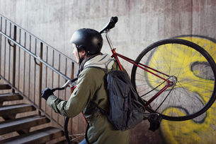 Sweden, Sodermanland, Stockholm, Sodermalm, Slussen, Mid adult man carrying bicycle upstairsの写真素材 [FYI02198845]