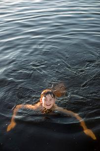 Sweden, Vastergotland, Lerum, Smiley boy (12-13) swimming in Lake Aspenの写真素材 [FYI02198870]