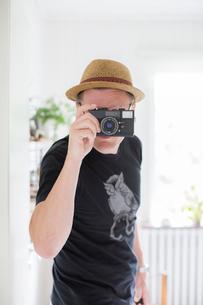 Sweden, Man wearing straw hat looking through photo cameraの写真素材 [FYI02198901]