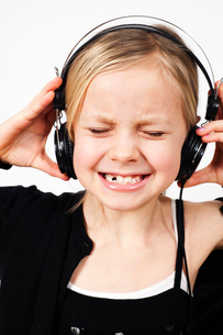 Girl (8-9) listening to music with great dissatisfactionの写真素材 [FYI02198902]