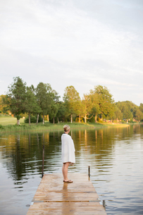 Sweden, Smaland, Braarpasjon, Mature woman wrapped in towel standing on jettyの写真素材 [FYI02198951]