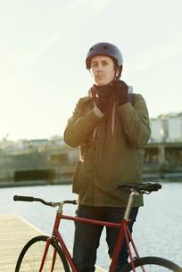 Sweden, Sodermanland, Stockholm, Sodermalm, Slussen, Outdoor portrait of mid adult man tying helmetの写真素材 [FYI02198972]