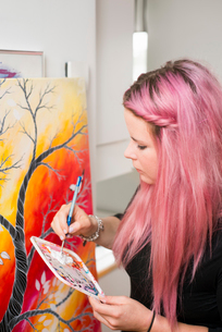 Sweden, Young woman with pink hair painting on canvasの写真素材 [FYI02199040]