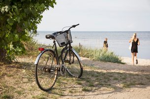 Sweden, Osterlen, Kivik strand, Bicycle and people at beachの写真素材 [FYI02199191]