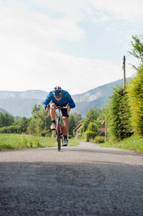 France, Rhone-Alpes, Haute-Savoie, Annecy, Male cyclist ride bike along road with mountains in backgの写真素材 [FYI02199238]