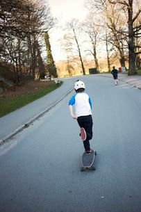 Sweden, Gothenburg, Slottsskogen, Rear view of boy (12-13) riding skateboard in parkの写真素材 [FYI02199240]