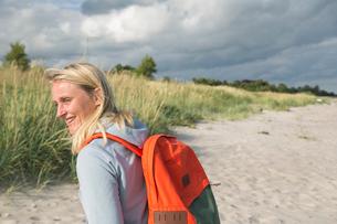 Sweden, Skane, Soderslatt, Beddinge, Smiley woman with backpack under cloudy skyの写真素材 [FYI02199273]