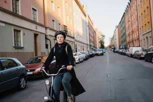 Sweden, Sodermanland, Stockholm, Sodermalm, Heleneborgsgatan, Young woman cycling on streetの写真素材 [FYI02199359]