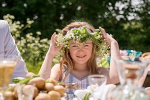 Sweden, Skane, Portrait of girl (8-9) adjusting flower wreathの写真素材 [FYI02199383]