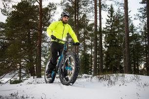 Finland, Pohjanmaa, Pietarsaari, Man on bicycle in forestの写真素材 [FYI02199391]