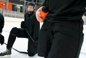 Sweden, Young hockey player wearing helmet kneeling on rinkの写真素材 [FYI02199406]