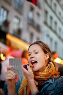 France, Paris, Young woman applying lipstick on city streetの写真素材 [FYI02199458]