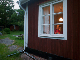 Sweden, Smaland, Horn, Girl (6-7) visible in traditional Swedish house windowの写真素材 [FYI02199462]