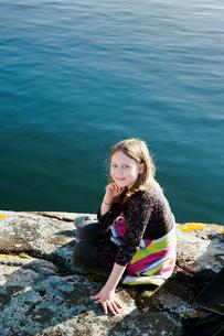 Sweden, Bohuslan, Smogen, Portrait of girl (8-9) sitting on rocky beachの写真素材 [FYI02199469]