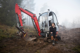 Sweden, Uppland, Nacka, Woman sitting by bulldozer and using phoneの写真素材 [FYI02199480]