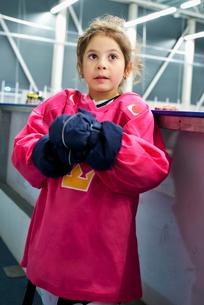 Sweden, Girl (4-5) in ice hockey uniform standing by railingの写真素材 [FYI02199524]