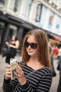 Denmark, Copenhagen, Teenage girl ( 16-17) using smart phoneの写真素材 [FYI02199562]