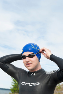 Sweden, Ostergotland, Vikbolandet, Man putting on swimming gogglesの写真素材 [FYI02199577]