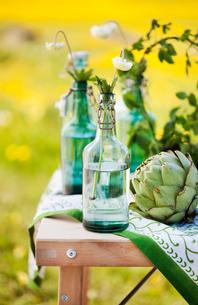 Sweden, Uppland, Flower in bottle and artichoke on tableの写真素材 [FYI02199617]