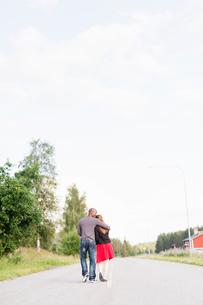 Sweden, Vastmanland, Bergslagen, Hallefors, Rear view of mid adult couple walking on rural roadの写真素材 [FYI02199618]