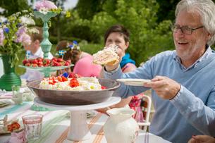 Sweden, Skane, Family with one child (8-9) having dessert outdoorsの写真素材 [FYI02199624]