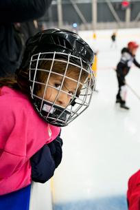 Sweden, Girl (4-5) in ice hockey uniform leaning on railingの写真素材 [FYI02199636]