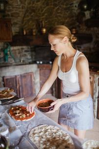 Italy, Tuscany, Woman preparing homemade pizzasの写真素材 [FYI02199681]