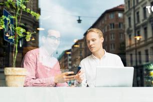 Sweden, Uppland, Stockholm, Two men talking in cafeの写真素材 [FYI02199687]