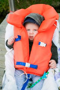 Sweden, Portrait of baby boy (6-11 months) in life jacketの写真素材 [FYI02199735]