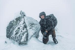 Sweden, Sylama, Jamtland, Young backpacker kneeling next to rock during snow blizzardの写真素材 [FYI02199743]