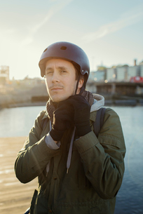 Sweden, Sodermanland, Stockholm, Sodermalm, Slussen, Outdoor portrait of mid adult man tying helmetの写真素材 [FYI02199767]
