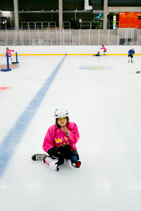 Sweden, Young female hockey player (6-7) sitting on iceの写真素材 [FYI02199785]