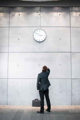 Sweden, Skane, Malmo, Businessman checking time at railroad stationの写真素材 [FYI02199792]