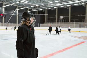 Sweden, Young hockey player wearing helmet standing on rinkの写真素材 [FYI02199808]