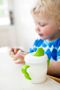 Baby bottle on table, girl (2-3) eating sandwich in backgroundの写真素材 [FYI02199817]