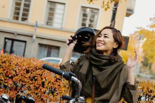 Sweden, Uppland, Stockholm, Vasastan, Rodabergsbrinken, Young woman taking off protective helmetの写真素材 [FYI02199857]