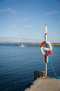 Sweden, Skane, Hallands Vadero, Ship heading to shore and life ring on foregroundの写真素材 [FYI02199905]