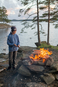 Sweden, Vastergotland, Lerum, Boy (12-13) making bonfire by lake Harsjon at sunsetの写真素材 [FYI02199914]
