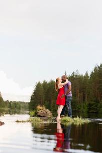 Sweden, Vastmanland, Bergslagen, Svartalven, Mid adult couple kissingの写真素材 [FYI02199923]