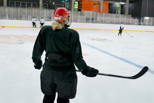 Sweden, Young hockey player with hockey stick standing on rinkの写真素材 [FYI02199927]