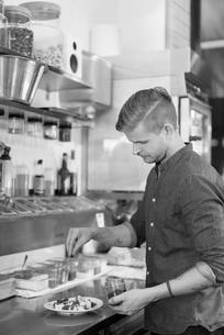 Sweden, Waiter sprinkling chocolate over dessertの写真素材 [FYI02199931]